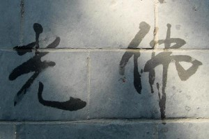 """Buddha's Light"" written by an old man with a water-brush on the floor (Summer Palace/Beijing)."